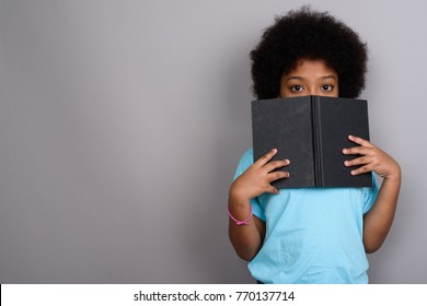 Studio shot of young cute African girl against gray background