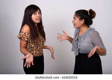 Studio shot of young fat Persian teenage girl looking at confused young Persian woman against gray background