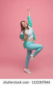 Studio shot of young female in colorful clothes in headphones and sunglasses listening music with smartphone dancing and smiling