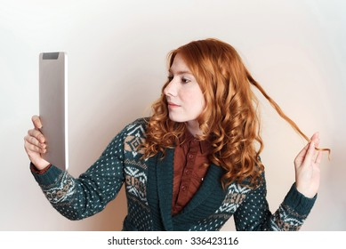 studio shot of young female making selfie using tablet on white background