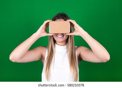 studio shot of a young, female model looking through cardboard virtual reality (VR) headset, and smiling. isolated on green screen