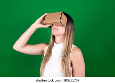 studio shot of a young, female model looking through cardboard virtual reality (VR) headset. isolated on green screen