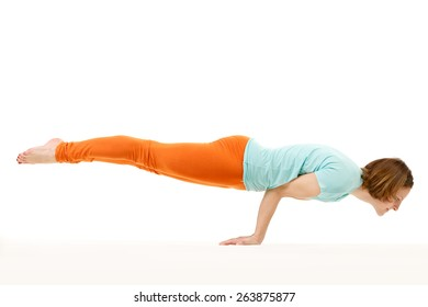 Studio shot of a young fit woman doing an arm balance yoga exercise.