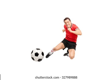 Studio shot of a young football player shooting a football towards the camera isolated on white background