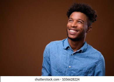 Studio shot of young handsome African man wearing smart casual clothing against brown background
