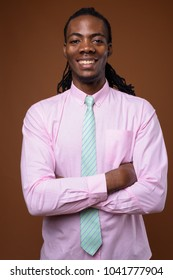 Studio shot of young handsome African businessman wearing pink shirt against brown background