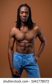Studio shot of young handsome African man shirtless against brown background