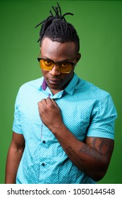 Studio shot of young handsome African man from Kenya against green background
