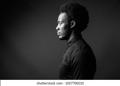 Studio shot of young handsome African businessman against gray background in black and white