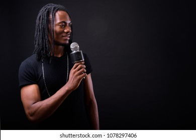 Studio shot of young handsome African man with dreadlocks against black background