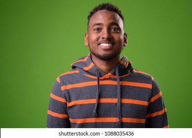 Studio shot of young handsome African man against green background