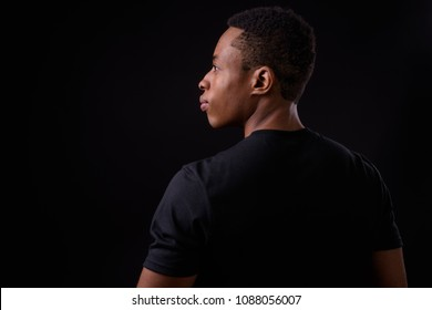 Studio shot of young handsome African man against black background