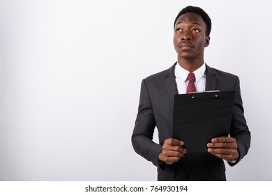Studio shot of young handsome African businessman wearing suit against white background