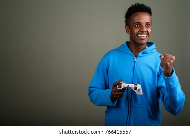 Studio shot of young handsome African man wearing hoodie against colored background