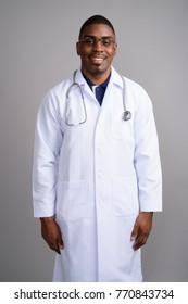 Studio shot of young handsome African man doctor against gray background