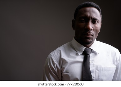 Studio shot of young handsome African businessman against gray background