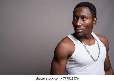 Studio shot of young handsome African man against gray background