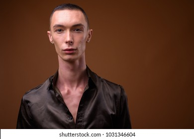 Studio shot of young handsome androgynous businessman wearing black satin shirt against brown background