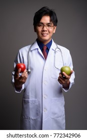 Studio shot of young handsome Asian man doctor wearing eyeglasses against gray background