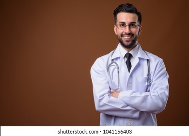 Studio shot of young handsome bearded Iranian man doctor against brown background