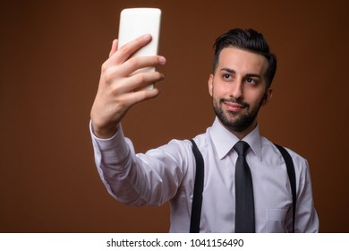 Studio shot of young handsome bearded Iranian businessman against brown background