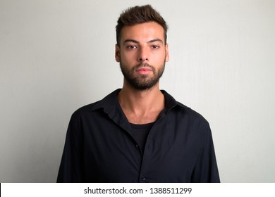 Studio shot of young handsome bearded businessman