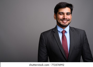 Studio shot of young handsome bearded Persian businessman against gray background
