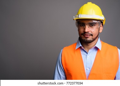 Studio shot of young handsome bearded Persian man construction worker against gray background