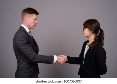 Studio shot of young handsome businessman and young beautiful Asian businesswoman wearing eyeglasses against gray background