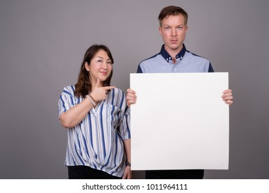 Studio shot of young handsome businessman and mature Asian businesswoman against gray background