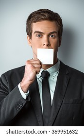 Studio shot of young handsome businessman. Businessman looking at camera and hiding mouth behind visit card