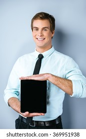 Studio shot of young handsome businessman. Businessman smiling, looking at camera and showing tablet computer