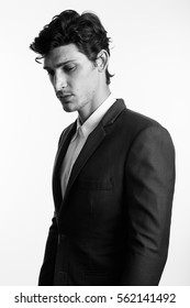 Studio shot of young handsome businessman thinking while looking down in black and white