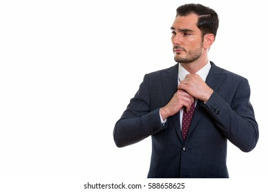 Studio shot of young handsome businessman thinking and looking away while fixing his tie