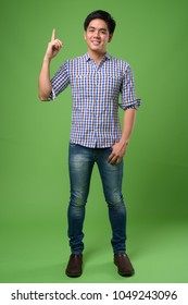Studio shot of young handsome Filipino man against green background