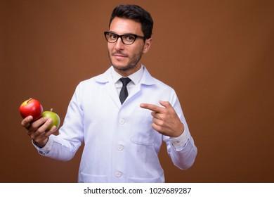 Studio shot of young handsome Hispanic man doctor wearing eyeglasses against brown background