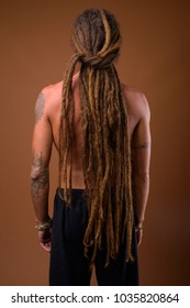 Studio shot of young handsome Hispanic man with dreadlocks shirtless against brown background