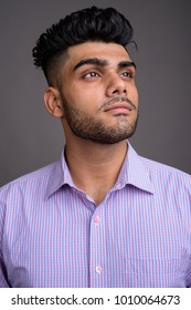 Studio shot of young handsome Indian businessman against gray background