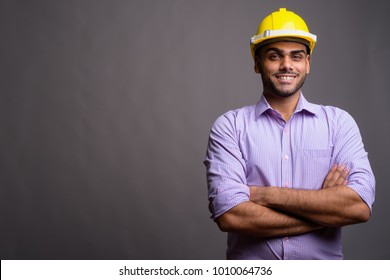 Studio shot of young handsome Indian businessman wearing hardhat against gray background