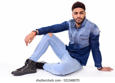 Studio shot of young handsome Indian man sitting on floor isolated against white background