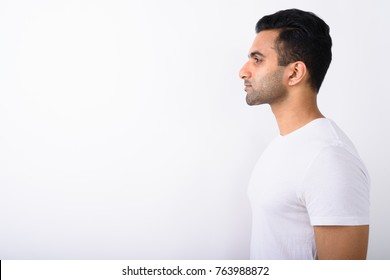 Studio shot of young handsome Indian man against white background