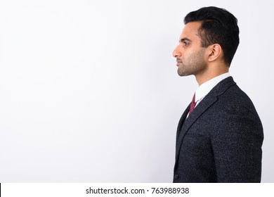 Studio shot of young handsome Indian businessman against white background