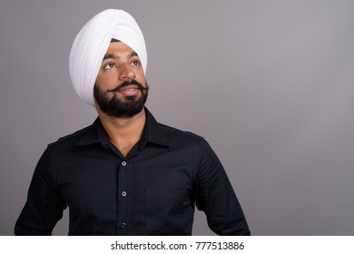Studio shot of young handsome Indian Sikh businessman wearing turban against gray background