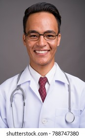 Studio shot of young handsome Indian man doctor wearing eyeglasses against gray background