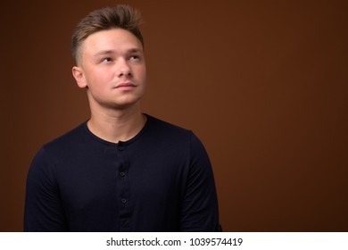 Studio shot of young handsome man wearing black shirt against brown background