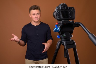 Studio shot of young handsome man vlogging against brown background
