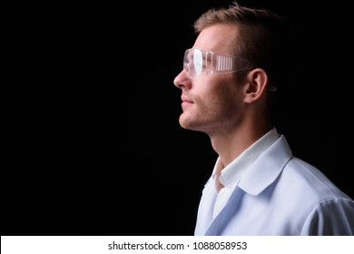 Studio shot of young handsome man doctor with blond hair wearing protective glasses against black background