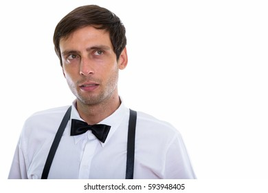 Studio shot of young handsome man thinking and looking up while wearing suspenders and bow tie