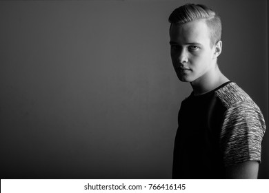 Studio shot of young handsome man against gray background in black and white