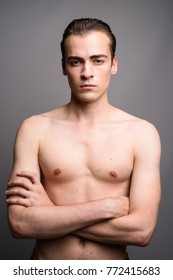 Studio shot of young handsome man shirtless against gray background